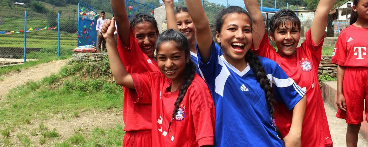 Group of girls in Nepal, outside smiling and cheering