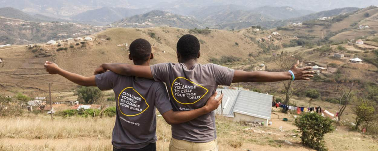 Two volunteers with their back to the camera looking at a view