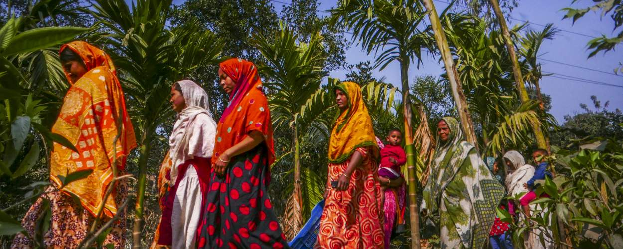 A group of female farmers dressed in bright colours walk along a sandy path