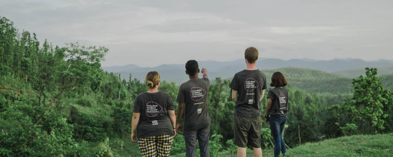 ICS volunteers stand with their back to the camera on top of a Nepalese green hill