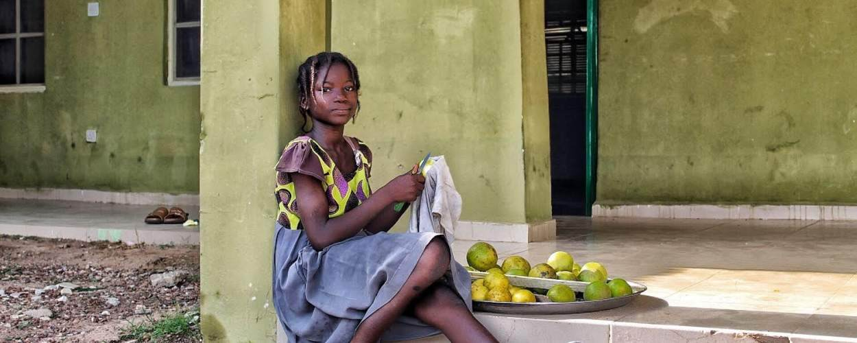 A young girl sits in the shade preparing fruit to sell to the volunteers