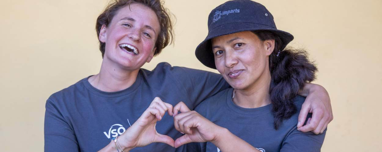 Two team leaders from the UK and Nepal sit together and form a heart shape with their hands