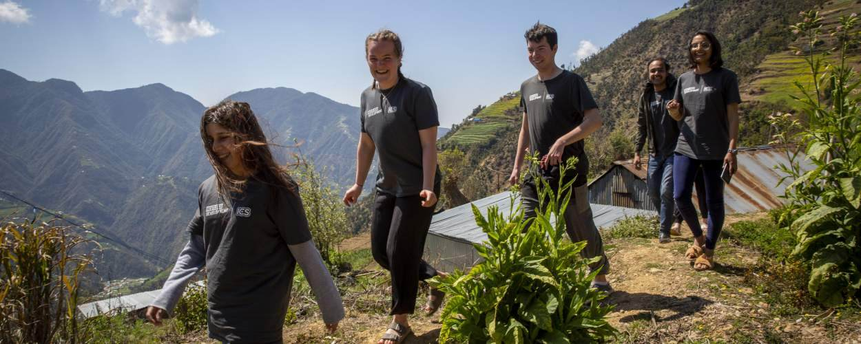A group of ICS volunteers walk along a path in a mountainous region of Nepal