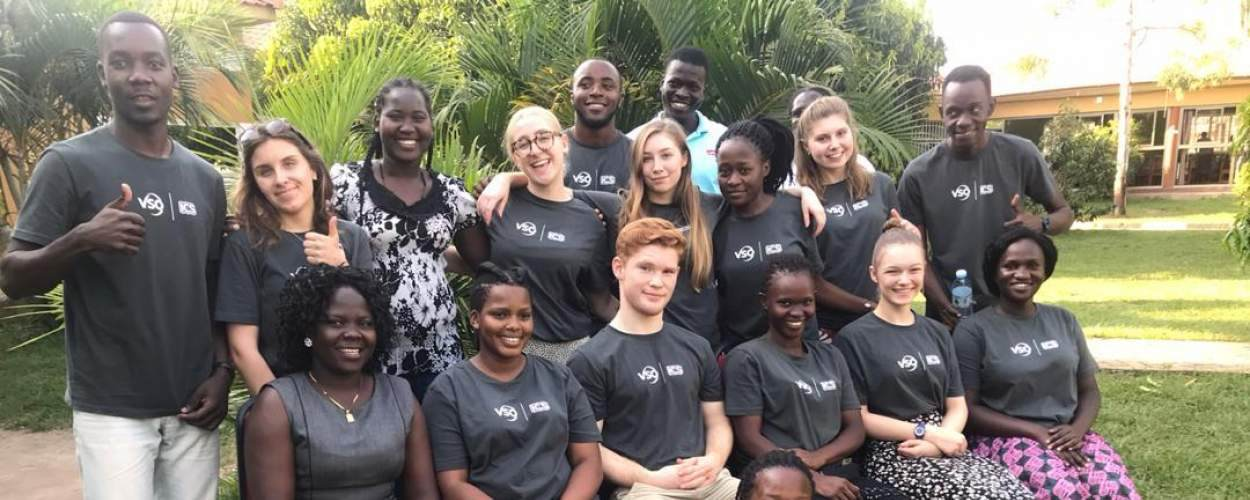 A group of volunteers sit for the camera, smiling and wearing ICS T-shirts whilst on placement in Uganda.