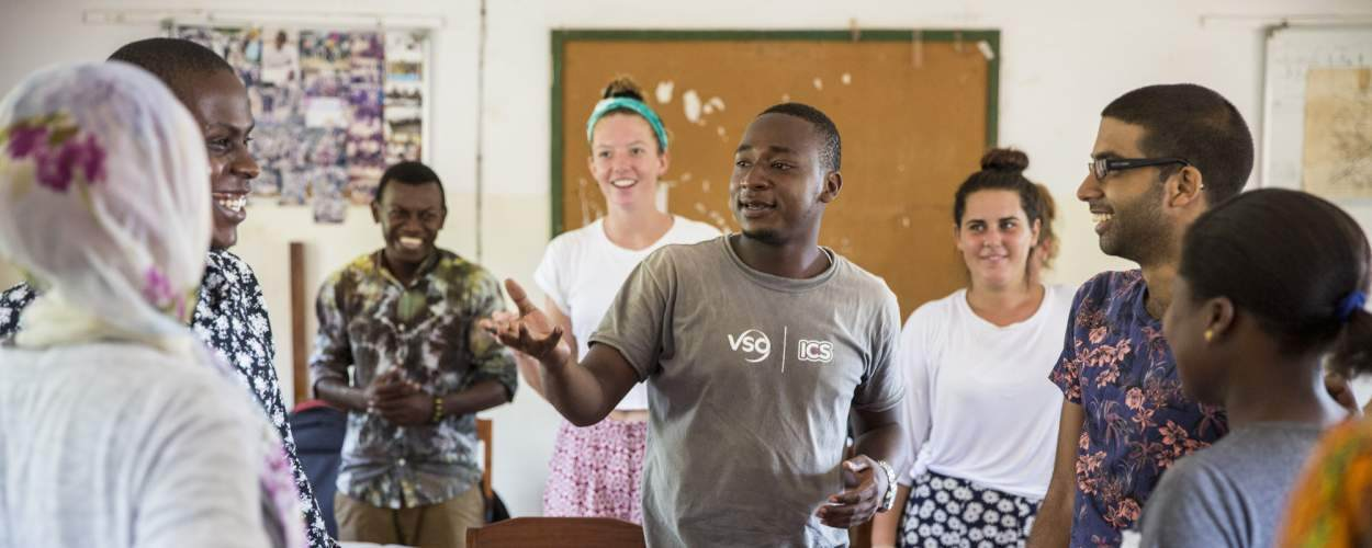 ICS volunteers stand in a group in a classroom as they take part in an Active Citizenship Day in Lindi, Tanzania