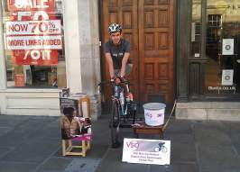 Volunteer completing a sponsored challenge on a static bike in their local high street.