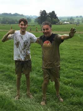 Two men stand in a field covered in mud