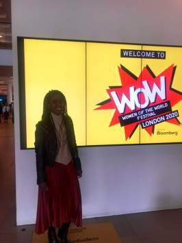 grace is stood in front of a sign for the Women of the world event