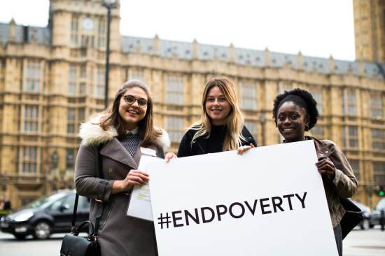 Tatch stands outside the UK parliament with a sign reading #NOPOVERTY