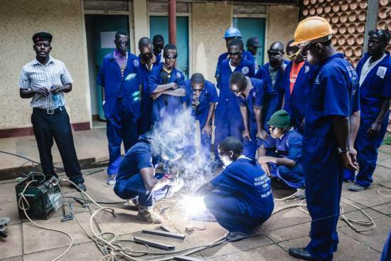 Students of a welding outreach centre demonstrate their skills to a local youths during a careers fair