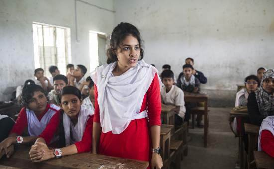 A schoolgirl in Bangladesh stands up in front of her class