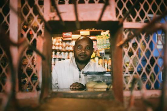 A tuck shop owner looks through the metal protective grate towards the camera