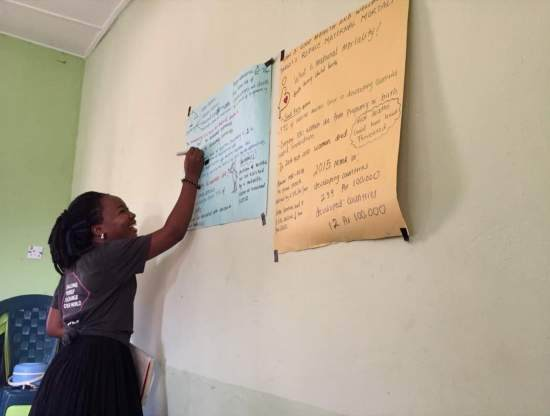 A volunteer writes on paper on the wall of a classroom