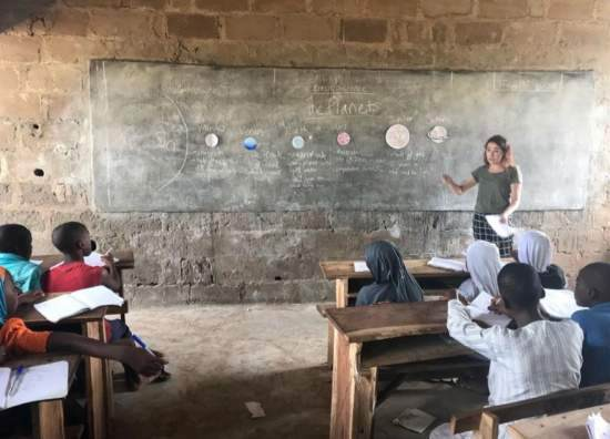 A volunteer teaches a classroom of primary school students