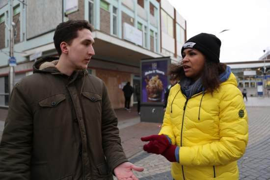 Two volunteers engage in a debate on the high street