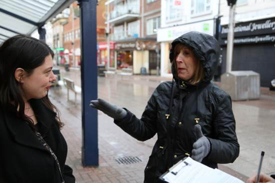 A woman talks with a volunteer out on a high street in Southend