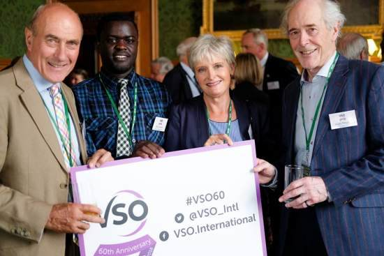 Felix inside the UK Parliament with some retired VSO long-term volunteers, holding a placard