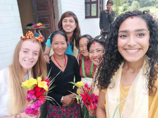 A group of volunteers dressed in traditional outfit holding Nepali flowers