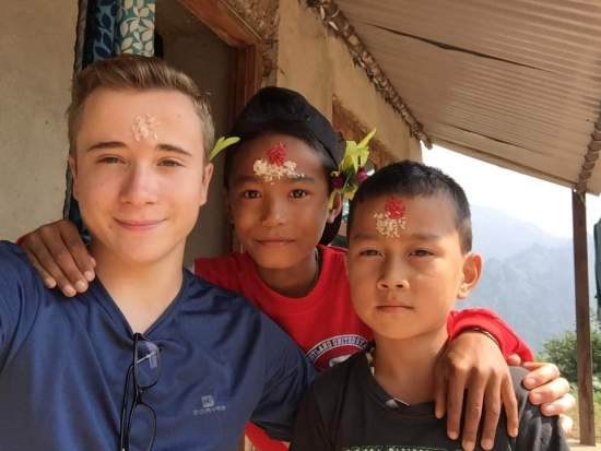 A UK volunteers stands beside his two Nepali host brothers