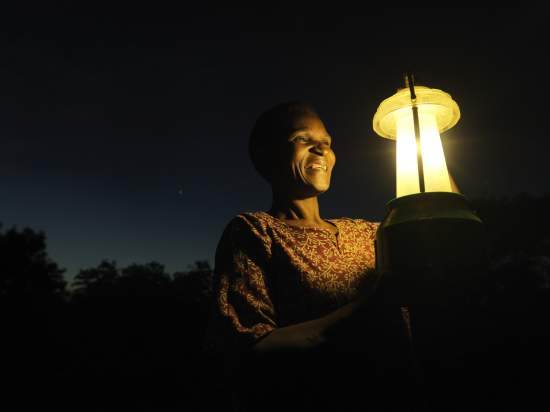 A Malawian woman holds up a lamp in front of her face