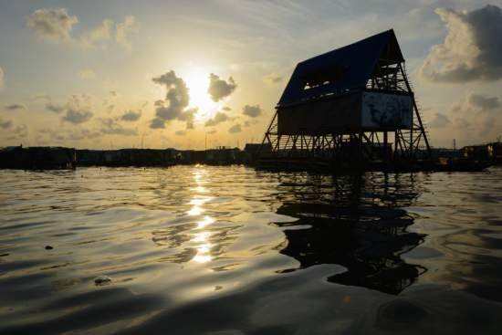 A triangular floating school on a pontoon set against the evening sunset