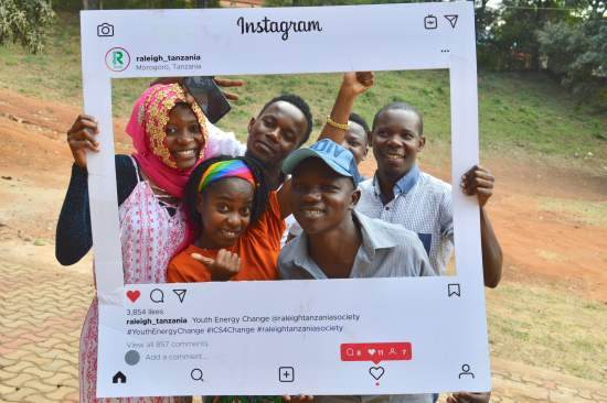 A group of young people hold up an Instagram photo frame and pose