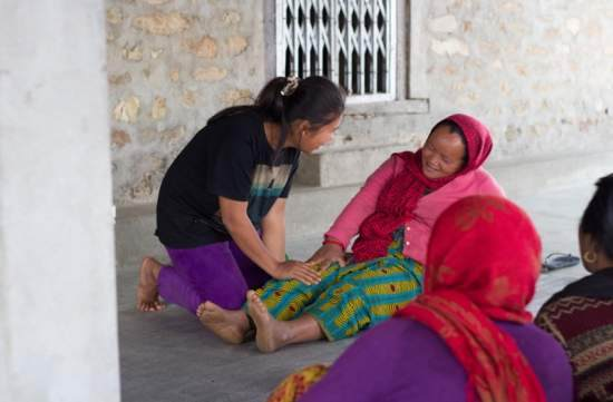 An ICS volunteer teaches a local woman first aid skills
