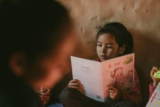 A young Nepalese girl sits against a wall and reads a book