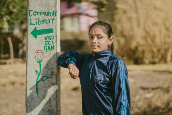 A young Nepalese girl poses for a photo next to a sign reading 'Community Library'