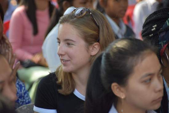 A girl looks to the side while sat down amongst a crowd