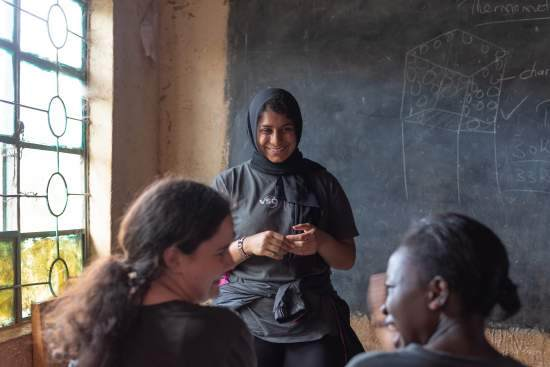 An ICS volunteer wearing a hijab smiles at the front of a dark classroom