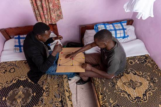 Two Kenyan ICS volunteers sit on a bed and play a board game