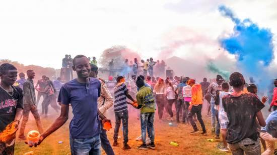 Young people throw coloured paint in a big community celebration