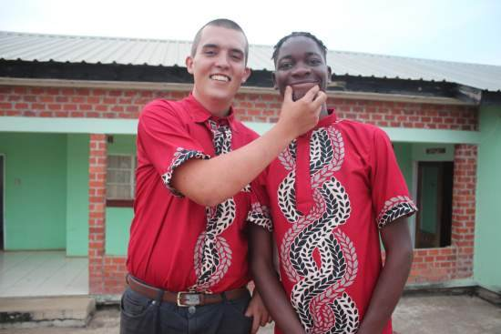Two volunteers in matching outfits stand together, one pulling the mouth of the other into a smile