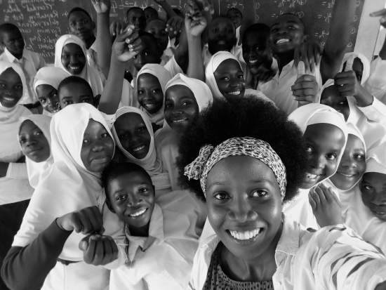 An excited group of schoolchildren pose for a selfie with volunteer Glory