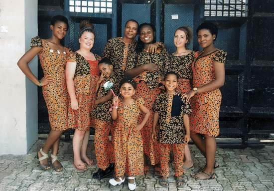 A UK volunteer poses for a photo with her extended Nigerian host family