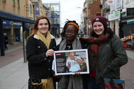 Three volunteers hold a placard in the middle of a shopping street