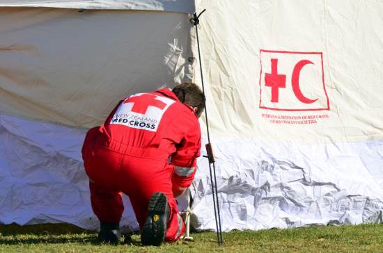 A Red Cross volunteer erects a tent