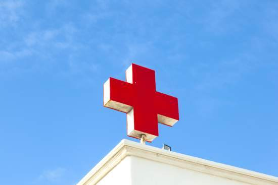 The sign of the red cross sits on top of a building
