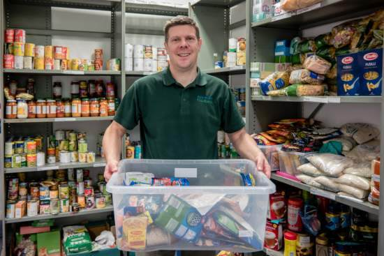 A Trussell Trust foodbank volunteer stands by shelves of products