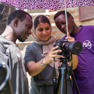A volunteer holding a camera shows the screen to two volunteers