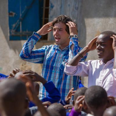 two male volunteers leading an outdoor session with school children