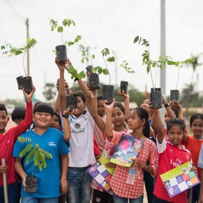 Children in Cambodia hold up saplings as they excitedly wait to plant them