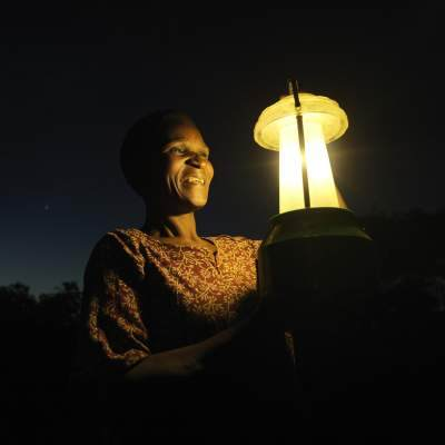 A Malawian woman holds a solar lamp with the background of the night sky